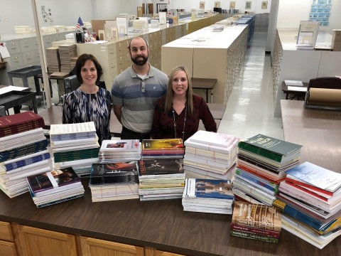 Melissa Luck (President, Luck's Music Library), Andy Luck (Vice President, Luck's Music Library), Amy King (Sales and Marketing Manager, Luck's Music Library) pictured in the Luck's Music Library warehouse with a large portion of music being donated to Texas schools.